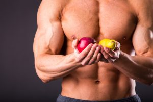 ripped guy holding fruits