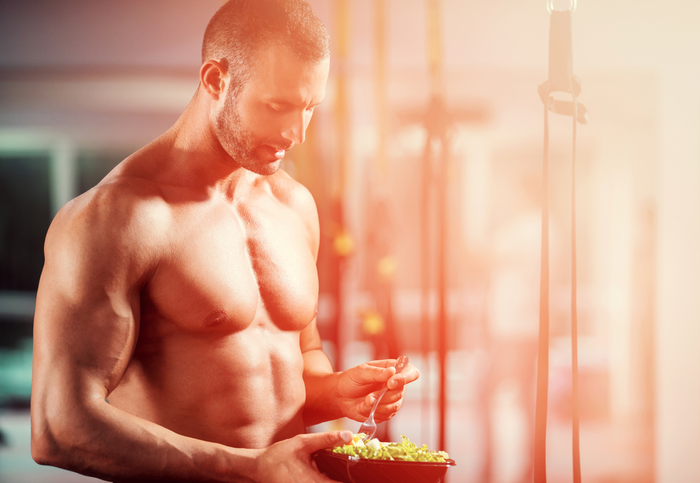 healthy man eating salad in gym